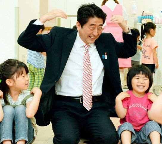 资料图:日本首相安倍晋三在视察横滨托儿所时和孩子们一起玩耍.