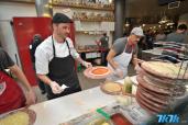 制作披萨的厨师们正在忙碌着。
